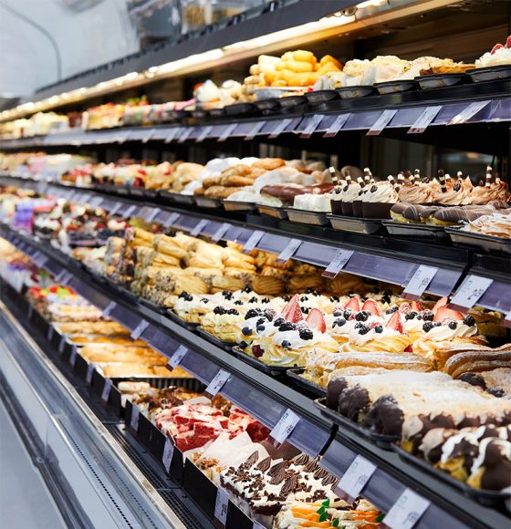 freshly baked cakes, cupcakes, tarts, eclairs and other desserts in the bakery