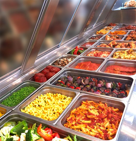 Hot plates counter with a variety of freshly made pasta, vegetables, meat kebabs and skewers