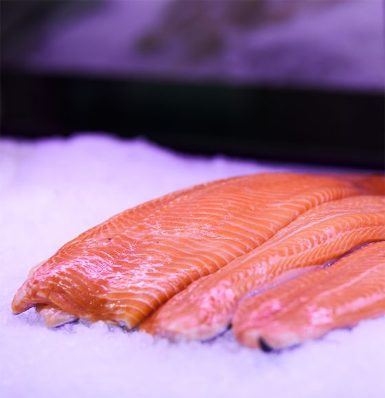 Fresh atlantic salmon fillets on ice in the seafood section